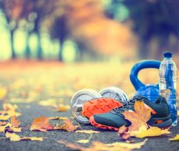 image of outdoor walking path lined with fall color trees with leaves on ground next to a pair of shoes, one water bottle, one kettle bell and one dumbbell
